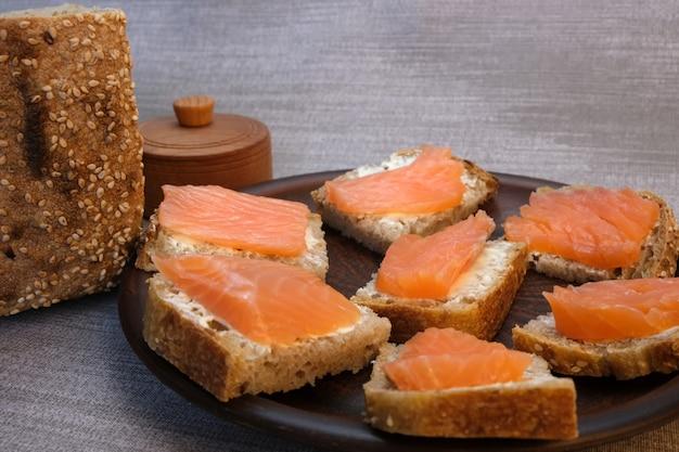 Pequenos sanduíches no pão caseiro com manteiga e peixe vermelho