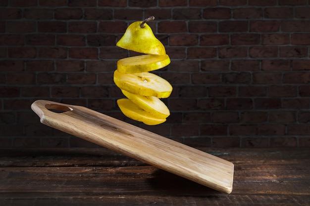 Pêra com tábua voando sobre fundo de madeira. limão cortado em rodelas e levitado no ar