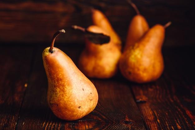 Pera dourada na mesa de madeira e algumas peras