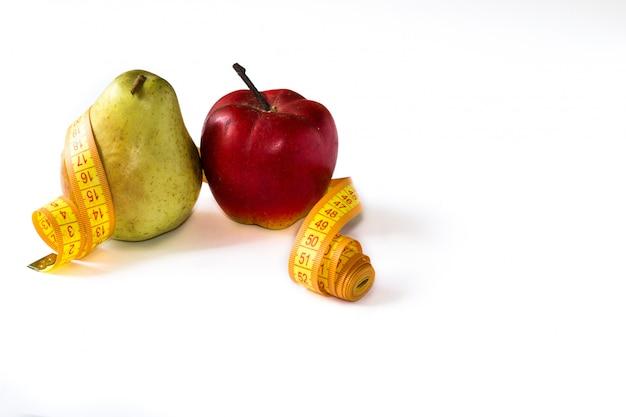 Pera e maçã vermelha amarrada com a fita do centímetro isolada no fundo branco.