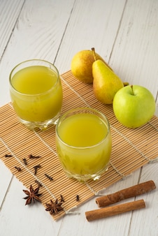 Pêra e suco em copos de vidro na mesa de madeira