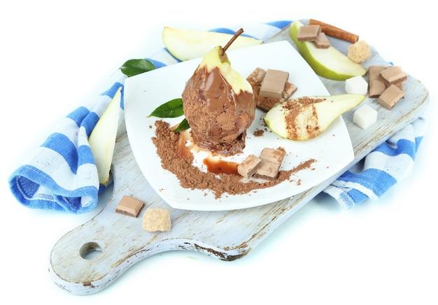 Pêra em chocolate no prato na placa de madeira no guardanapo isolado no branco
