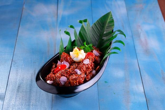 Peralan de frango ou curry de frango seco kerala prato especial de frango disposto em uma talheres preta