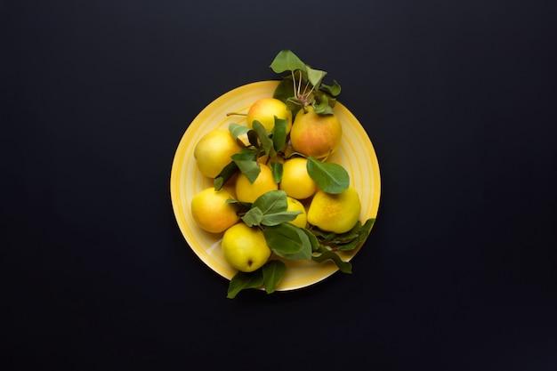 Peras amarelas maduras com folhas em um prato amarelo no escuro