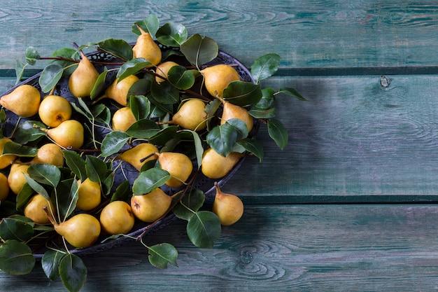 Peras amarelas maduras em um velho vaso e ramos de pêra