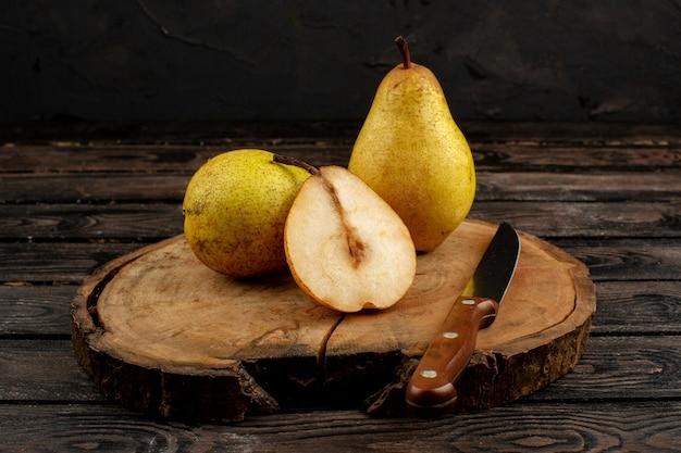 Peras amarelo maduro maduro suculento em uma mesa de madeira e marrom rústico
