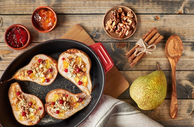 Peras assadas com queijo roquefort, nozes e geléia na madeira