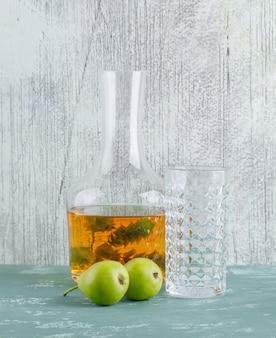 Peras com bebida à base de plantas, copo vazio em gesso e parede suja, vista lateral.