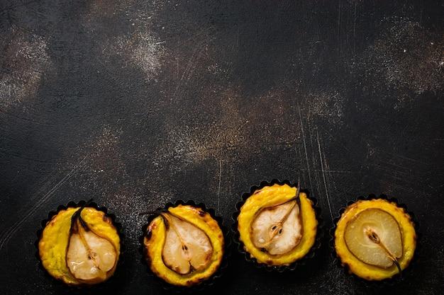 Peras e mini tortas de creme em um fundo de mesa velha de concreto marrom escuro. vista do topo.
