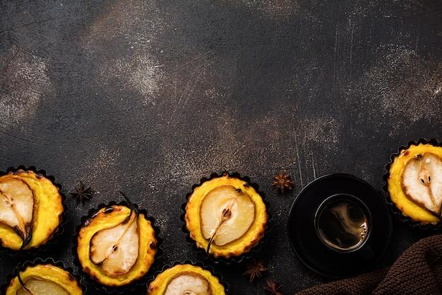 Peras e mini tortas de creme em um fundo de mesa velha de concreto marrom escuro.