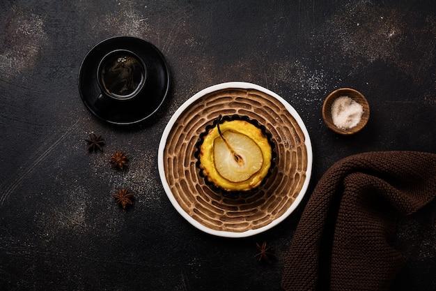 Pêras e mini tortinhas de creme em um fundo de mesa velha de concreto marrom escuro