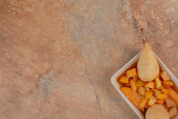 Peras e tigela de geléia de frutas na mesa de mármore laranja.
