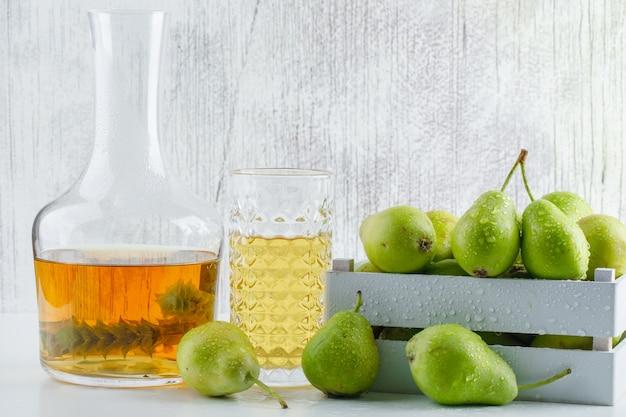 Peras em caixa de madeira com vista lateral de bebida em uma parede branca e suja