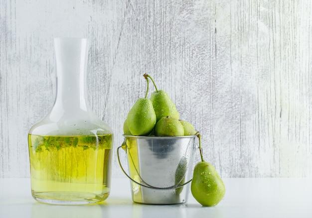 Peras em um mini balde com vista lateral para bebidas à base de plantas em fundo branco e sujo