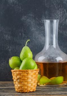 Peras em uma cesta com sidra beber vista lateral na parede de madeira e suja