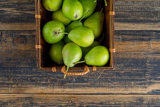 Peras em uma cesta plana leigos sobre um fundo de madeira