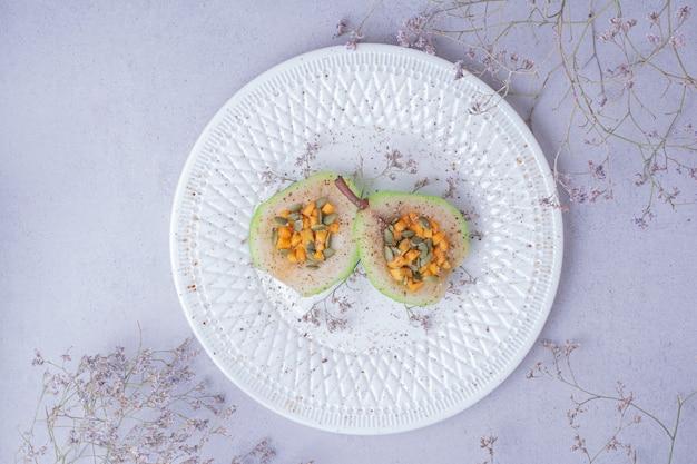 Peras fatiadas com cenoura picada e sementes em um prato branco