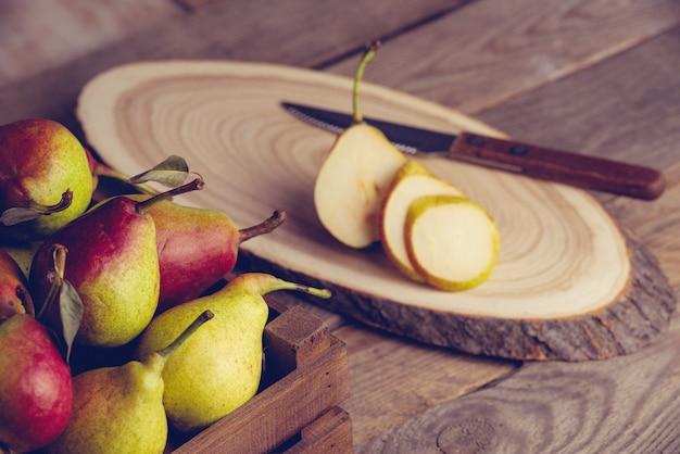 Peras frescas com folhas em uma caixa de madeira com fundo de madeira.