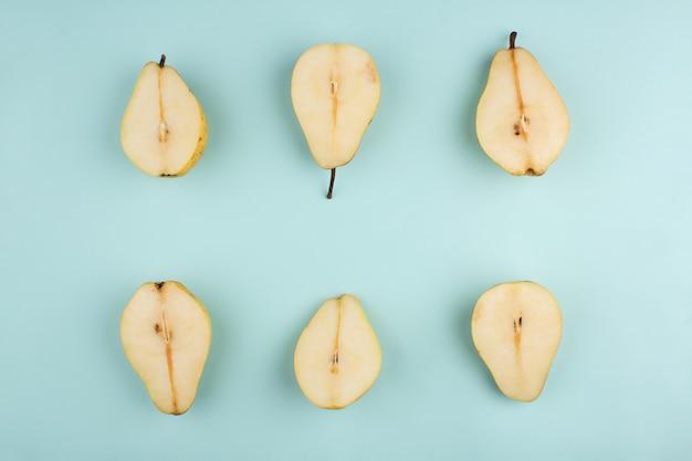 Peras frescas cortadas maduras em um azul