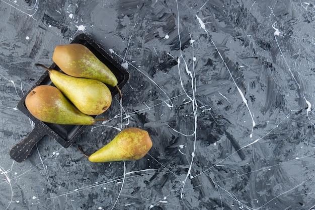 Peras frescas maduras em uma placa de madeira colocada no fundo de mármore.