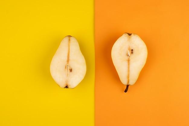 Peras frescas maduras meio corte no chão colorido