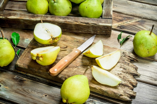 Peras frescas na bandeja e pêra fatiada na tábua de corte com faca na mesa de madeira