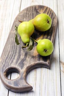 Peras frescas na tábua de madeira marrom.