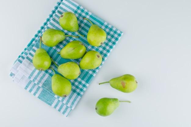 Peras frescas no branco e no fundo de toalha de cozinha. configuração plana.