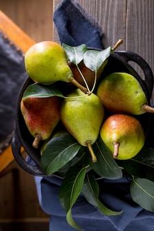 Peras maduras com folhas de pera verde em uma mesa de madeira. conceito de colheita