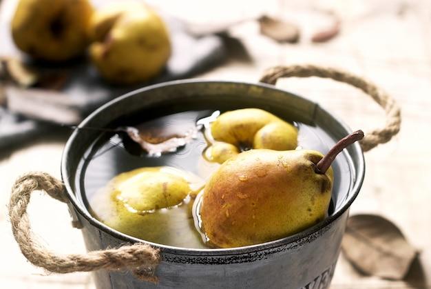 Peras maduras e folhas de pera em um balde de ferro com água e sobre uma mesa de madeira. estilo rústico.