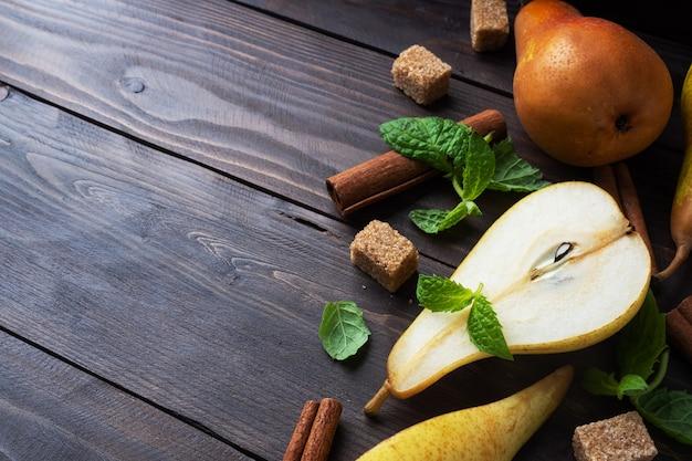 Peras maduras e suculentas amarelas com canela na madeira