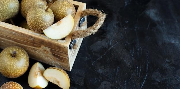 Peras nashi (peras maçã ou peras asiáticas) em um fundo escuro