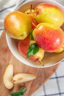Peras orgânicas estabelece em um pano de cozinha levemente pontilhada
