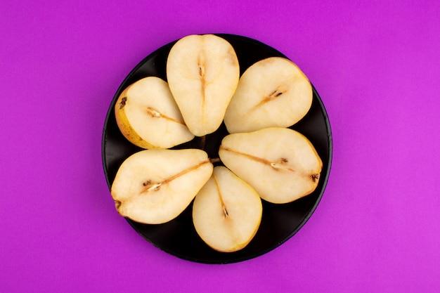 Peras redondas em forma de frutas maduras dentro de chapa preta em uma mesa roxa