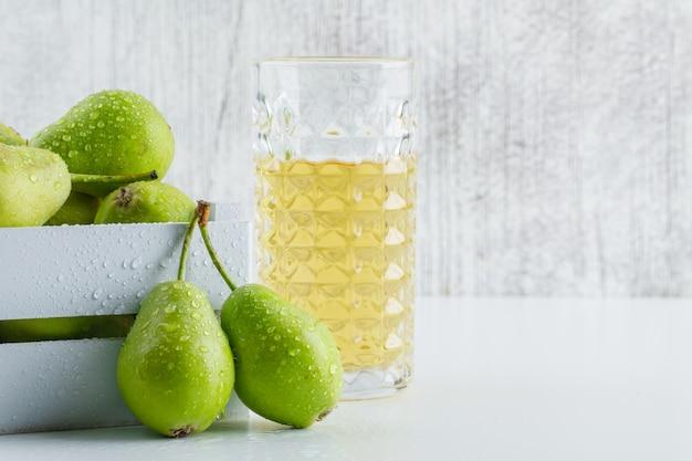 Peras verdes com bebida em uma caixa de madeira no fundo branco e sujo, vista lateral.