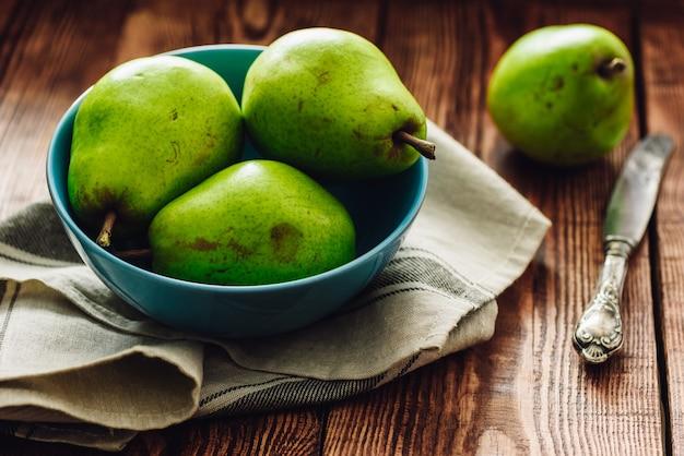 Peras verdes em tigela azul e faca na mesa.