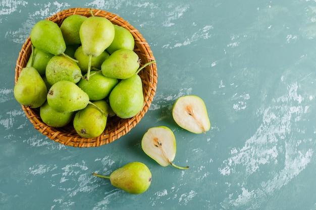 Peras verdes em uma cesta na superfície de gesso
