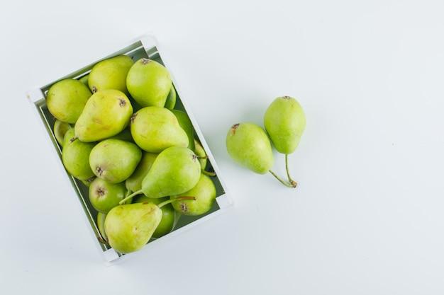 Peras verdes em uma vista superior de caixa de madeira em um fundo branco