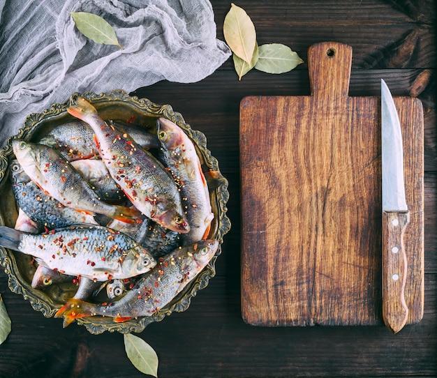 Perca de peixe de rio fresco e crucian em uma chapa de ferro