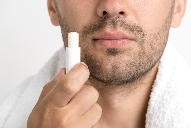 Perca-se do homem com uma toalha em volta do pescoço, segurando protetor labial