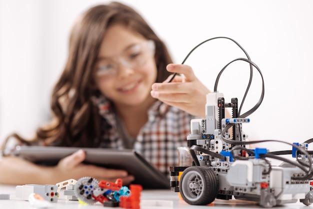 Percebendo minha invenção. alegre menina superdotada sentada na sala de ciências e usando dispositivos enquanto estuda e tem aulas de tecnologia