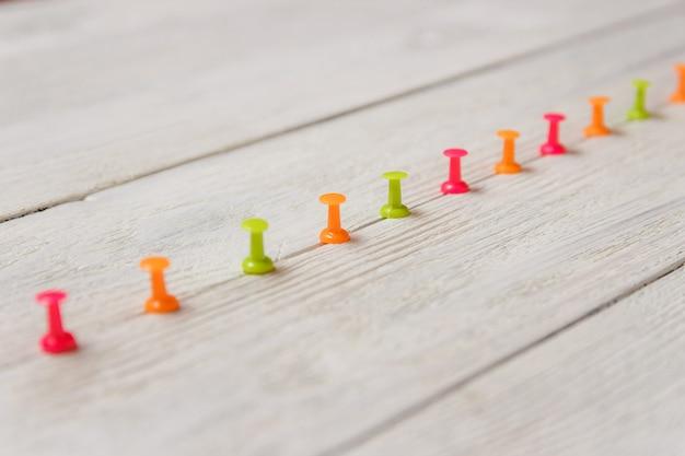 Percevejos coloridos dispostos na fileira de gama alta no fundo de madeira branco, espaço da cópia. papelaria. conceito de negócio de ascensão.