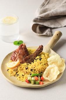 Perda de arroz kebuli (nasi kabli ou briyani) em fundo de creme, coberto com frango assado e passas.