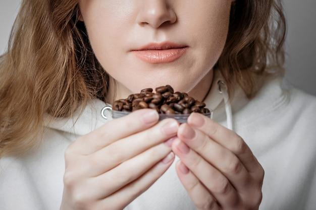 Perda de cheiro. feche o retrato de uma jovem mulher caucasiana, farejando os grãos de café isolados. conceito de coronavírus