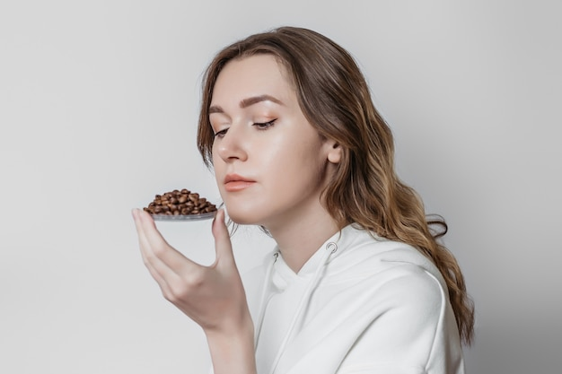 Perda de cheiro. jovem mulher cheirando grãos de café isolados.
