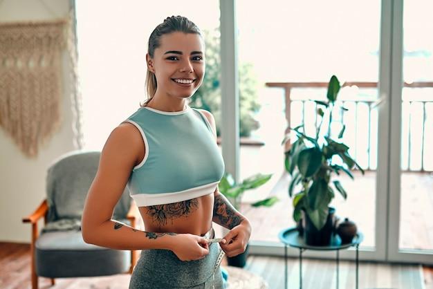 Perda de peso, corpo magro, conceito de estilo de vida saudável. mulher jovem esguia medindo sua cintura fina com uma fita métrica em casa na sala de estar.