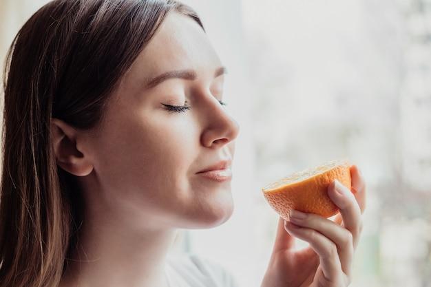 Perda do conceito de cheiro. feche o retrato de uma jovem caucasiana em pé perto da janela e cheirando uma laranja