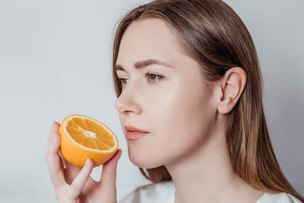Perda do conceito de cheiro. feche o retrato de uma jovem mulher branca segurando uma laranja perto do nariz isolada