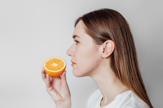 Perda do conceito de cheiro. feche o retrato de uma jovem mulher caucasiana, segurando uma laranja perto de seu nariz isolado. copie o espaço. vista de perfil