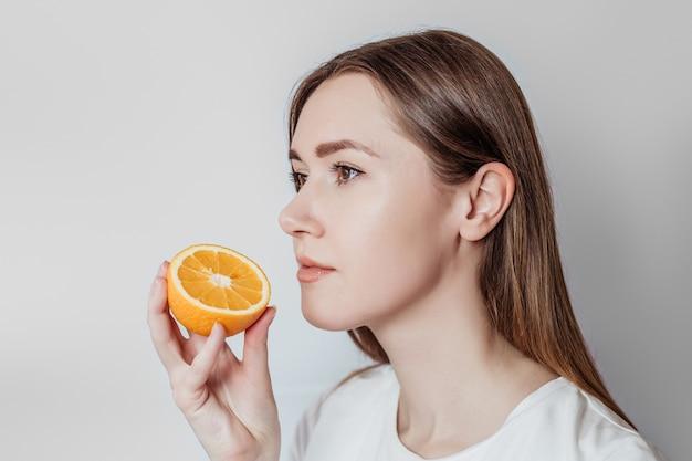 Perda do conceito de cheiro. feche o retrato de uma jovem mulher caucasiana, segurando uma laranja perto de seu nariz isolado. copie o espaço